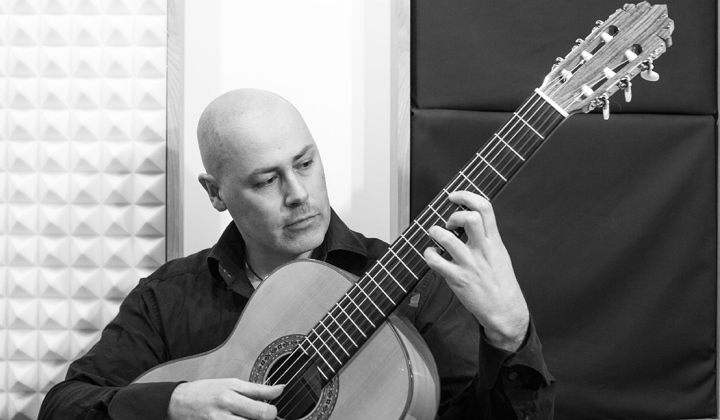 Black and white photograph of Martyn playing traditional Spanish guitar